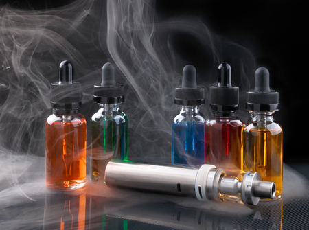 Electronic cigarette and vape liquids within vapor on black background Foto de archivo