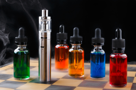 Electronic cigarette and bottles with vape liquid within vapor on chessboard and black background