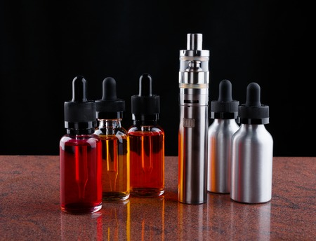 Electronic cigarette and bottles with vape liquid on granite surface and black background