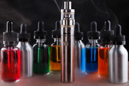 Electronic cigarette and vape liquids within vapor on granite surface and black background Stock Photo