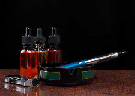 Electronic cigarette on ashtray, cigarette lighter and bottles