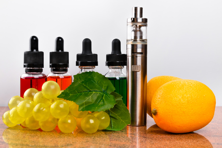 Electronic cigarette, bottles with vape liquid, lemons and fake bunch of grapes on granite surface and white background Stock Photo