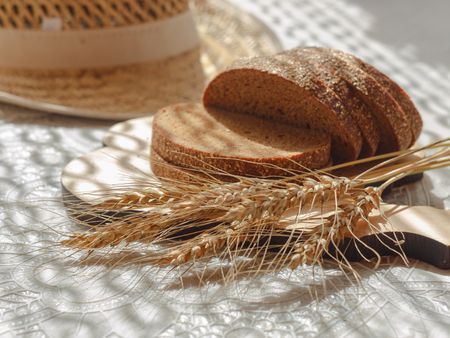 sliced bread with wheat spikelets on wooden chopping board and blurred straw hat on background
