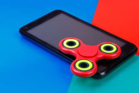 Fidget spinner lying on smartphone. Multicolored background Stock Photo