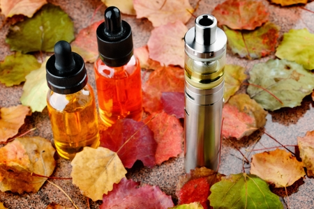 Electronic cigarette and vape liquids on wooden table with autumn leaves