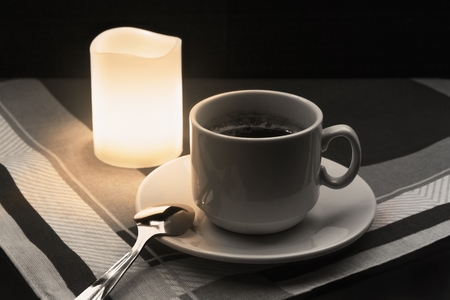 Cup of coffee with spoon and candle on fabric background