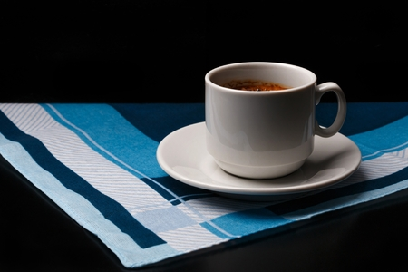 White cup of coffee on fabric background