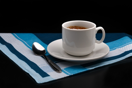 White cup of coffee and spoon on fabric background