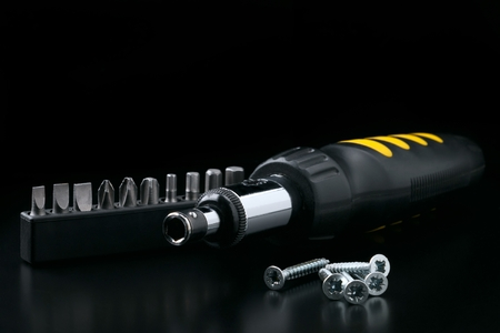 Screwdriver with bitset and tapping screw on black background