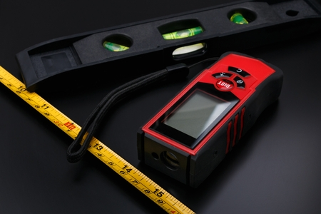 Tape measure, laser tape and building level on black matte surface