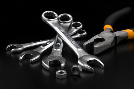Spanner set and pliers on black background