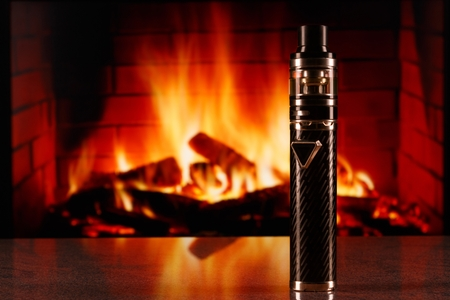 modern black electronic cigarette on fireplace background