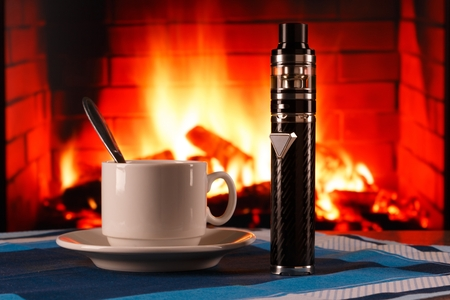 electronic cigarette and cup of coffee on fireplace background