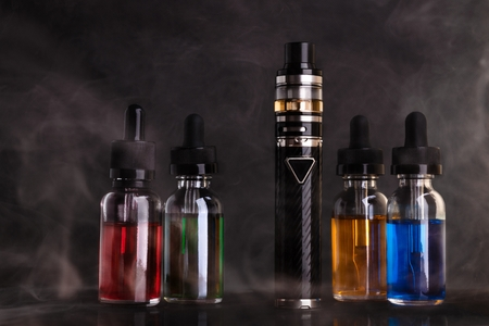 Electronic cigarette and bottles with vape liquid within vapor on black background 版權商用圖片