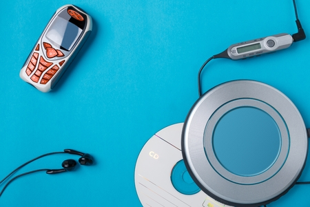 personal cd player with remote control and mobile phone on blue background 版權商用圖片