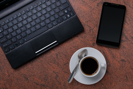 laptop computer with smartphone and cup of coffee on granite surface