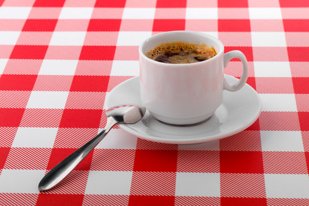 Cup of coffee on white and red checkered tablecloth