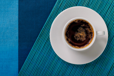 Top view of a black coffee cup on blue bamboo mat and fabric background