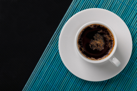 Top view of a black coffee cup on blue bamboo mat and black textured background.