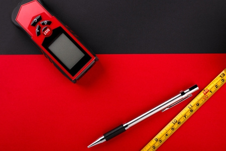 Tape measure, laser distance meter and pencil on matte black and red background