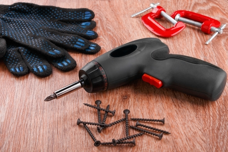 screwdriver with pile of screws, cloth gloves and clamps on wooden background 版權商用圖片