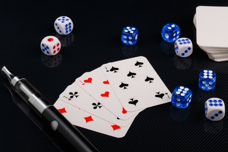 blue and white dices and cards with electronic sigarette on black glossy background