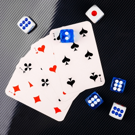 blue and white dices and cards on black glossy background. flat lay