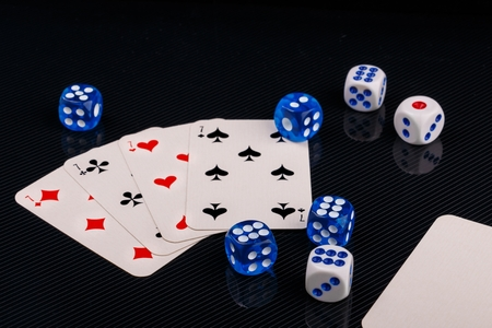 blue and white dices and cards on black glossy background
