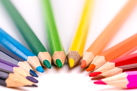 colored pencils lined with tips to the center in the form of an arch on white background