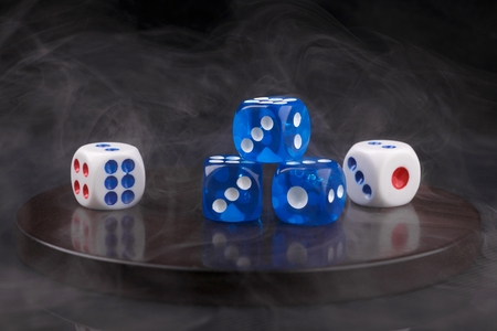 blue and white dices on round stone base in smoke. black background 版權商用圖片