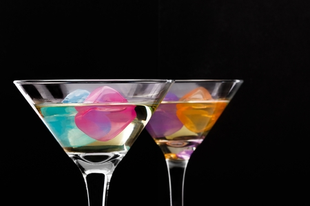 wine glasses with colored ice cubes on black background. Selective focus