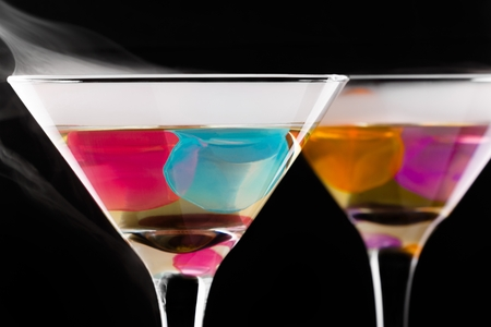 wine glasses with colored ice cubes and floated ice vapor on black background. Selective focus
