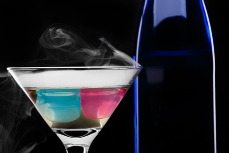 wine glass with colored ice cubes and dark blue bottle in floated ice vapor on black background