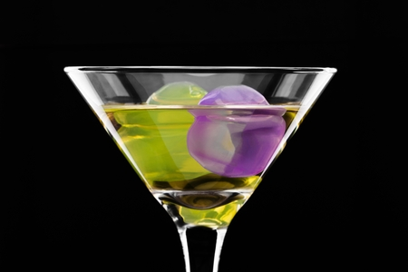 wine glass with colored ice cubes on black background