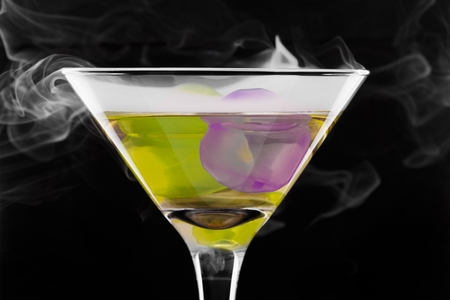 wine glass with colored ice cubes and floated ice vapor on black background