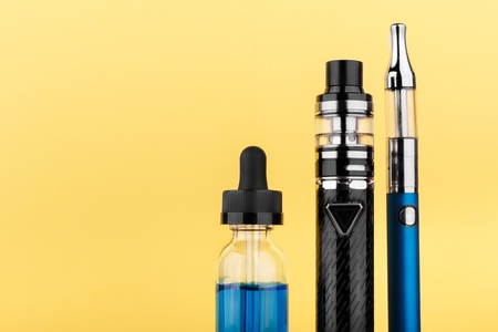 vaping device collection and bottle with blue vape liquid on yellow background. Close up 版權商用圖片