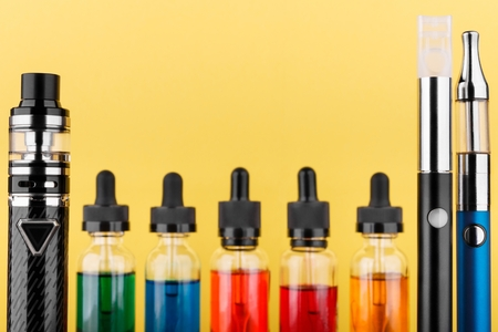 Closeup image of vaping device collection and bottles with colored vape liquid on yellow background. Selective focus