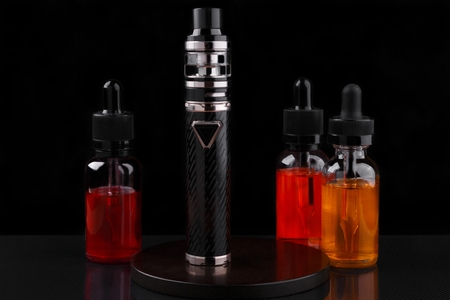 Electronic cigarette or vaping device and assorted vape liquids on black background