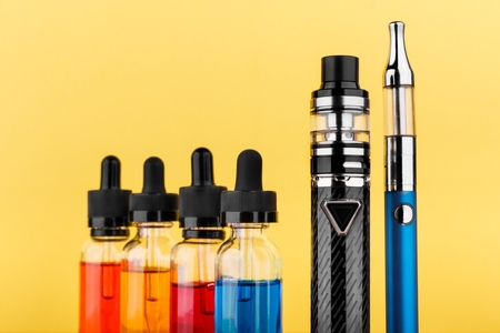 Close up image of two vaping devices and bottles with vape liquid on yellow background. Selective focus 版權商用圖片