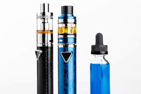 Electronic cigarettes and bottle with vape liquid on white background