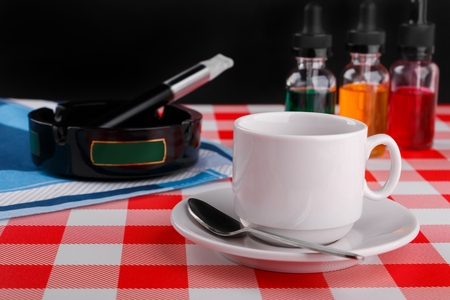 cup of coffee and electronic cigarette in ashtray with bottles of vape liquid on checkered tablecloth