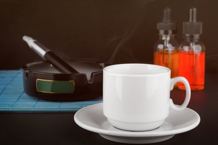 cup of coffee and electronic cigarette in ashtray with bottles of vape liquid on dark background