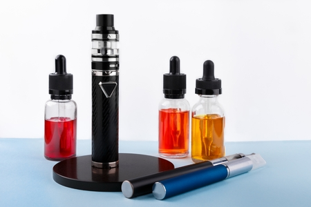 Electronic cigarettes and glass bottles with vape liquid on white background