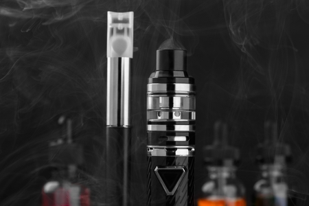 electronic cigarettes surrounded by vapor and blurred bottles with vape liquid on background