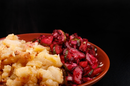 Boiled chopped potatoes and vegetable salad on clay plate. Foto de archivo
