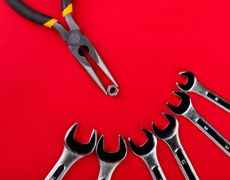 Pliers with nut and different-sized wrenches on red background. Concept of a bird feeding nestlings.
