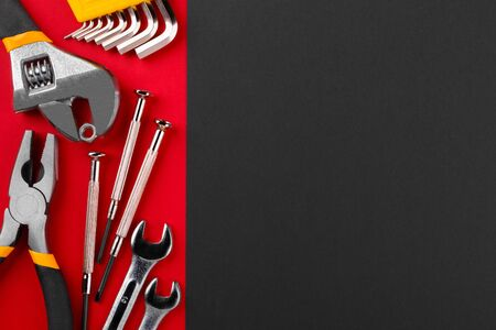 Working tools on red background with copyspace. Flat lay.