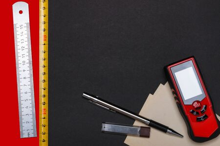 Measuring tools and automatic pencil with paper for notes on black and red background.
