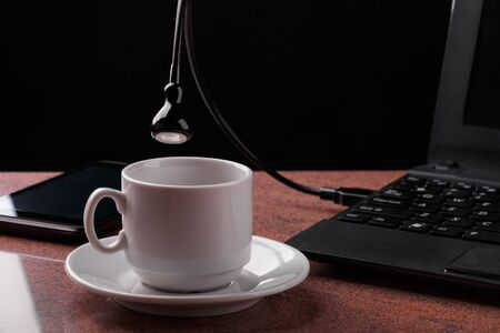 LED USB lamp connected to laptop and looking into coffee cup. Concept of alive usb-lamp. Black background