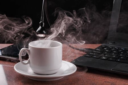 LED USB lamp connected to laptop and looking into coffee cup from which steam comes. Concept of alive usb-lamp.